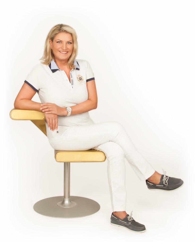 Dr. Doris Leukauf sitz auf einem gelben Stuhl